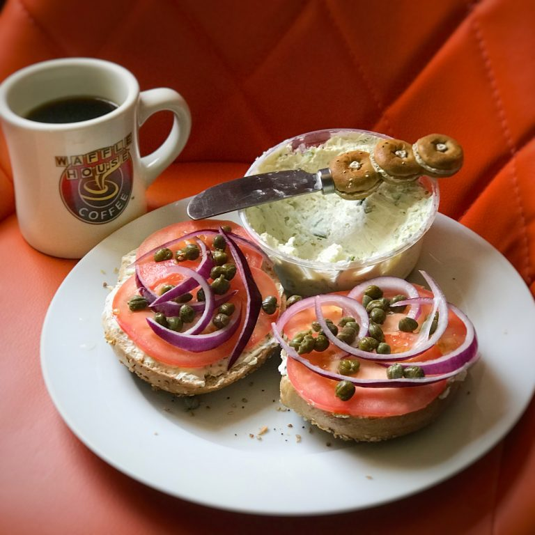 An open faced bagel sandwich with tomato, capers and onions and a Waffle House mug on an orange chair